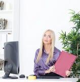 Młody blond bizneswoman z falcówką siedzi przy stołem przy biurem Obrazy Royalty Free