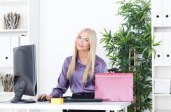 Młody blond bizneswoman z falcówką siedzi przy stołem przy biurem Fotografia Stock