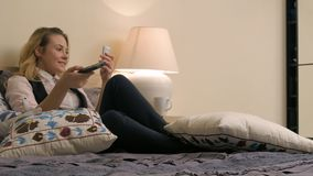 Młody blond kobiety lying on the beach na łóżkowym, używać smartphone i oglądający TV Zdjęcia Stock