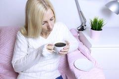 Młody blond kobiety obsiadanie na różowej kanapie i pić kawie fotografia royalty free