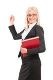 Młody blond nauczyciel trzyma kredkę i książkę Zdjęcia Stock