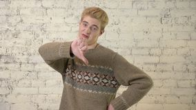 Młody blondie pokazuje niechęć znaka, kciuki zestrzela, niepowodzenie znak 60 fps zdjęcie wideo