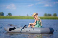 Młody blondynki dziewczyny połów na łodzi w jeziorze Zdjęcie Stock