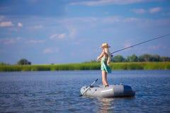 Młody blondynki dziewczyny połów na łodzi w jeziorze Fotografia Royalty Free