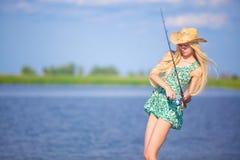 Młody blondynki dziewczyny połów w jeziorze Fotografia Stock