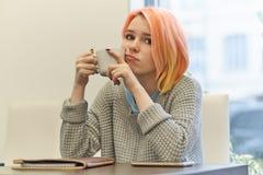 Młody blondynki kobiety dziewczyny ucznia obsiadanie przy stołem w cukiernianym dowcipie zdjęcie royalty free
