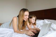 Młody blondynki kobiety lying on the beach w łóżku z małą córką w ranku i używać laptopie Obrazy Stock