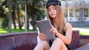 Młody blondynki obsiadanie na ławce pracuje na pastylka komputerze osobistym Żeński student collegu używa bezprzewodowego interne zbiory