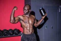 Młody Bodybuilder patrzeje jego mięśnie podczas gdy trzymający butelkę Obraz Stock