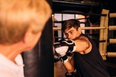 Młody bokser uderza uderza pięścią torbę obrazy stock