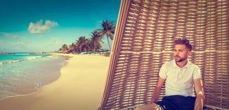 Młody broda mężczyzna w parasol przy tropikalną plażą obrazy royalty free