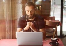 Młody Brodaty biznesmen Jest ubranym Czarnego Tshirt Pracującego laptopu Miastowej kawiarni Mężczyzna drewna stołu filiżanki kawy fotografia royalty free