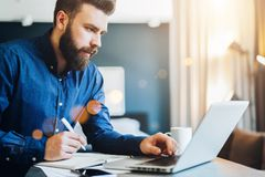 Młody brodaty biznesmen pracuje na komputerze, bierze notatki w notatniku, analizuje informację, robi planowi biznesowemu obraz stock