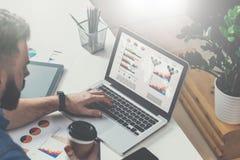 Młody brodaty biznesmen siedzi w biurze przy stołem, pisać na maszynie na laptopie z wykresami, diagramami i mapami na ekranie, zdjęcie stock