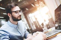 Młody brodaty biznesmen w szkłach pracuje za laptopem w a Obraz Stock