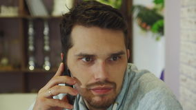 Młody brodaty biznesmen z popielatą bluzą sportowa pracuje w jaskrawym biurze zbiory