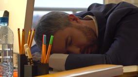 Młody brodaty biznesmena dosypianie w ranku przy jego miejscem pracy po pracować przez noc Obraz Stock
