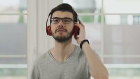 Młody brodaty facet słucha muzykę w hełmofonach, slowmotion zdjęcie wideo