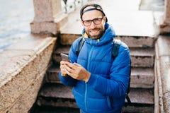 Młody brodaty facet stoi outdoors w czarnej nakrętce i błękitnym anorak mienia plecaku z telefonem komórkowym odizolowywającym na obrazy stock