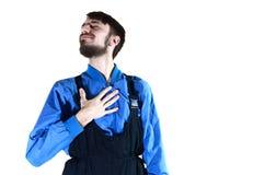 Młody brodaty facet w pracować mundurów punkty on z jego ręką zdjęcie royalty free