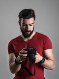 Młody brodaty fotograf przegląda fotografie na tyły lcd ekranie dslr kamera Fotografia Stock