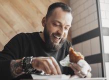 Młody brodaty mężczyzna łasowania hamburger i uśmiechnięty zakończenie up zdjęcie stock