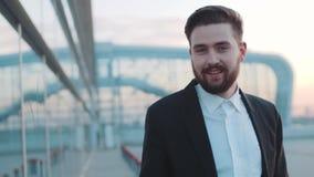 Młody brodaty mężczyzna bierze daleko okulary przeciwsłonecznych i daje szczęśliwemu uśmiechowi w kierunku kamery zdjęcie wideo