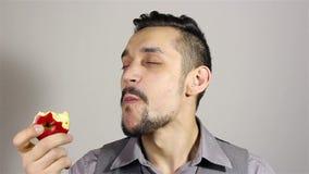 Młody brodaty mężczyzna je jabłka zbiory wideo