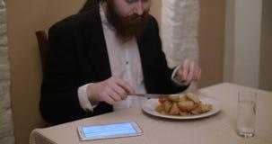 Młody brodaty mężczyzna je przy restauracją i use pastylką zbiory