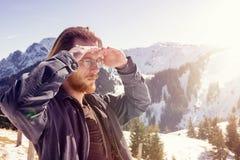 Młody brodaty mężczyzna otaczający górami patrzeje w dista Zdjęcia Stock