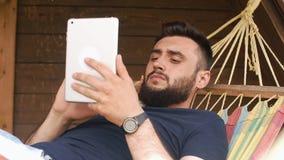Młody brodaty mężczyzna używa pastylkę, kłama w hamaku w dom na wsi zbiory wideo