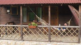 Młody brodaty mężczyzna używa pastylkę, kłama w hamaku w dom na wsi zdjęcie wideo