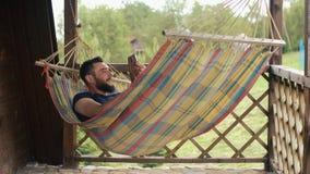 Młody brodaty mężczyzna używa pastylkę, komunikuje używać wideo konferencję, kłama w hamaku w dom na wsi zdjęcie wideo