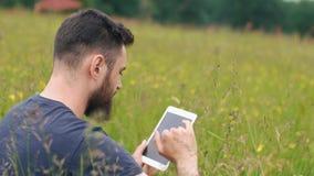 Młody brodaty mężczyzna używa pastylkę podczas gdy siedzący na trawie blisko dom na wsi zbiory