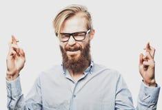 Młody brodaty mężczyzna utrzymuje palce krzyżujący obraz royalty free