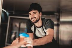 Młody Brodaty mężczyzna w fartuch pozycji w jedzenie ciężarówce Filiżanka kawy Uliczny karmowy pojęcie Jedzenie w miasteczku Sprz obrazy stock