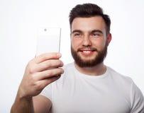 Młody brodaty mężczyzna z telefonem komórkowym obrazy stock