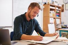 Młody brodaty męski nauczyciel przy biurka ocechowania studentsï ¿ ½ pracą Obrazy Stock