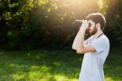 Młody brodaty męski patrzeć przez lornetek podczas gdy stojący przy zieleni polem, obserwuje coś Przystojny młody facet ma expedi Zdjęcia Royalty Free