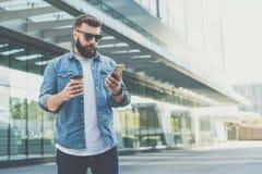 Młody brodaty modnisia biznesmen w okularów przeciwsłonecznych stojakach na miasto ulicie, chwyt filiżance kawy i uses smartphone obrazy stock