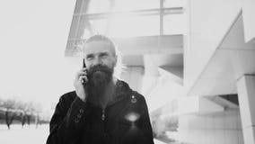 Młody brodaty modnisia mężczyzna koncentrował opowiadać na telefonie na citystreet, rozmowa blisko budynku biurowego Obraz Royalty Free