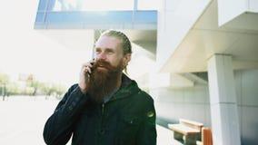 Młody brodaty modnisia mężczyzna koncentrował opowiadać na telefonie na citystreet, rozmowa blisko budynku biurowego Zdjęcie Stock