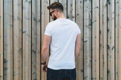 Młody brodaty modnisia mężczyzna ubierający w białych okularach przeciwsłonecznych i koszulce jest stojakami plenerowymi przeciw  zdjęcia royalty free