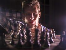 Młody brodaty szachowy grandmaster obsiadanie, główkowanie na kolejnym kroku w ciemnym pokoju i zdjęcia royalty free