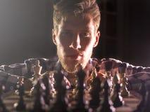 Młody brodaty szachowy grandmaster obsiadanie, główkowanie na kolejnym kroku w ciemnym pokoju i zdjęcia stock