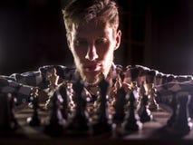 Młody brodaty szachowy grandmaster obsiadanie, główkowanie na kolejnym kroku w ciemnym pokoju i obrazy royalty free