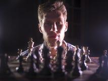 Młody brodaty szachowy grandmaster obsiadanie, główkowanie w drodze w ciemnym pokoju i zdjęcia royalty free