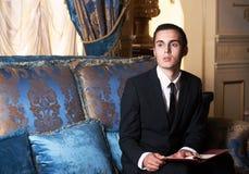 Młody brunet mężczyzna obsiadanie na kanapie Zdjęcia Royalty Free