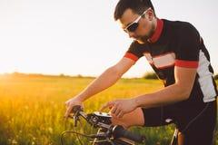 Młody brunetka facet na rowerze górskim używa kolarstwo komputer, nawigator w śródpolnym zmierzchu dzień Zdjęcia Stock