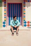 Młody brunetka mężczyzna, jest ubranym w błękitnej koszula, sandały, okulary przeciwsłoneczni, z torbą Zdjęcia Stock